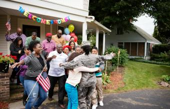 Female soldier embracing family