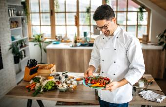 Young chef holding a plate