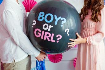"""Man and woman holding black balloon with """"boy or girl"""" on gender reveal party"""