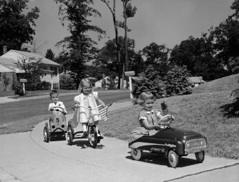 1950s kids riding toy cars and bikes on sidewalk
