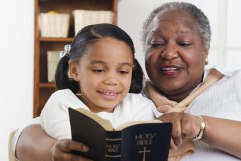 Woman reading the Bible to her granddaughter