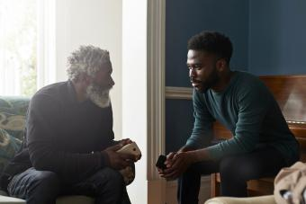Father and son talking while sitting in living room