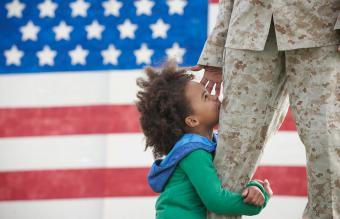 girl hugging leg of returning soldier