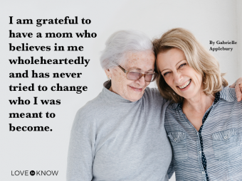Portrait of senior woman holding hands with daughter and mother's day quote