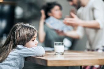 Little girl feeling sad while her parents are arguing in the background