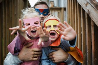 Portrait of children with father in superhero costumes
