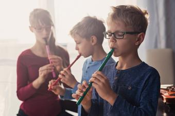Three kids playing flutes together