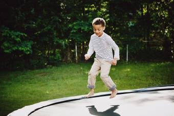 Smiling young boy jumping on trampoline