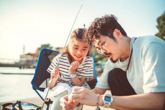 Young dad teaching her daughter fishing at pier joyfully