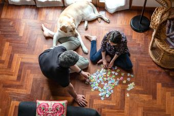 Father and daughter sitting on living room floor, doing jigsaw puzzle