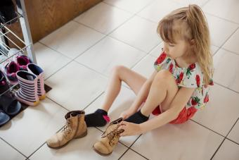 Child putting lace-up boots on herself