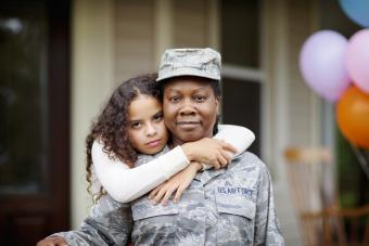 Daughter embracing her soldier mom against house