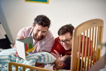 Adoptive fathers reading bedtime story to daughter