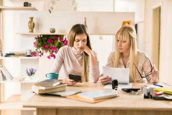 Worried mother and daughter calculating financial reports together
