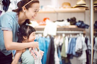 Pretty young mom trying on clothes with her lovely little daughter