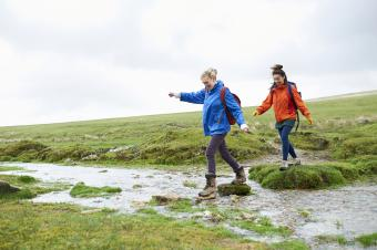 Two hikers crossing stream in countryside