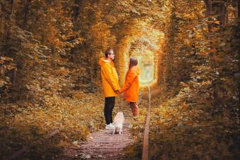 Happy young couple in raincoats with dog