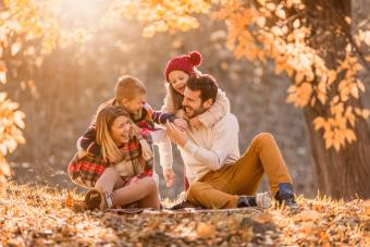 Playful family having fun in autumn day at the park