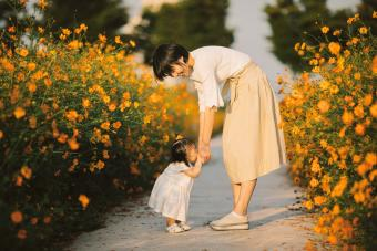 Happy mother with baby in yellow cosmos flower field