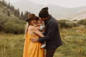 couple hugging toddler daughter in rural valley