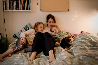Mother reading to daughters at bedtime