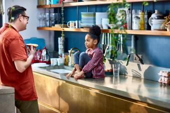 Young girl sitting on kitchen counter talking to father