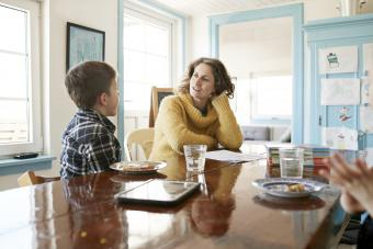 Mother and son eating and talking at dining table