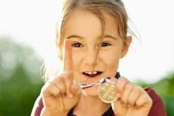 Excited little girl showing her winning medal and gesturing number one