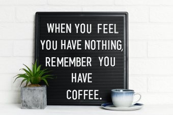 Letter board with cup of coffee and houseplant