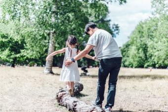 Caring single father assisting his daughter to walk along a tree trunk