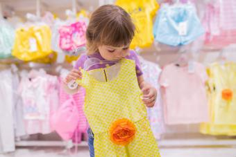 Adorable smiling little girl at the clothes store