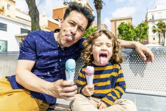 Happy father and son sitting on bench enjoying an ice cream