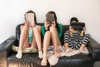 three kids with electronic devices on a sofa
