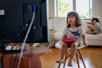 Three year old toddler eating in front of a television