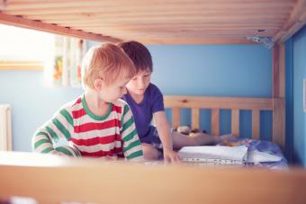 Brothers in pyjamas sitting on the lower bed of a bunk bed