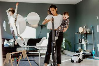 Woman carrying toddler and vacuum cleaning room