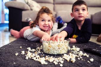Kids watching a home movie while eating popcorn