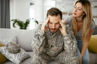 Depressed soldier sitting on sofa with his wife