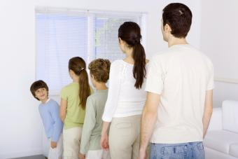 Family lined up shortest to tallest, youngest boy looking over shoulder at rest of family