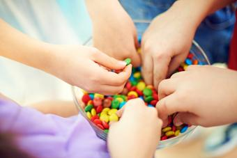 Hands of kids taking multi colored chocolate candies from bowl