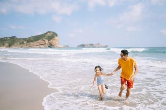 Father and daughter playing in waves on beach