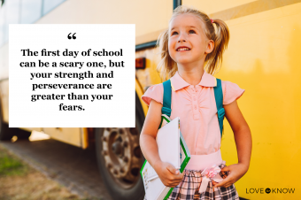 Little smiling girl with two ponytails and textbooks staying beside a yellow school bus