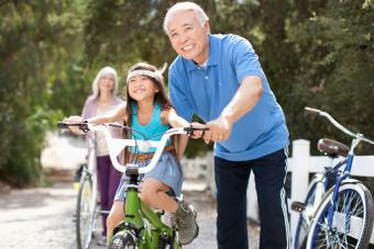 Grandfather granddaughter ride bicycle