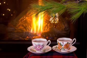 Antique teacups on tartan pattern scarf under Christmas tree in front of fireplace