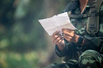 Female soldier reading letter among war