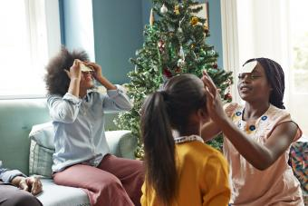 Sisters sticking adhesive notes on forehead while sitting in living room at home