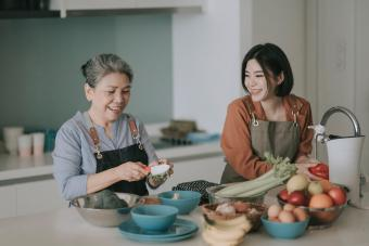 Woman and her mother getting ready cooking meals
