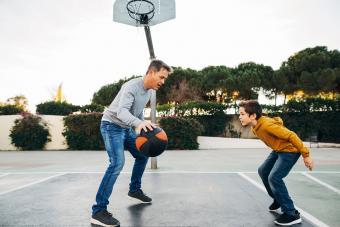 Men and boy playing basketball