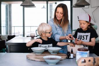 Children baking in the kitchen handling food with mother