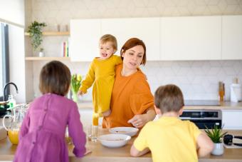 Mother with three small children indoors in kitchen in the morning at home